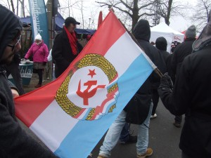 Die Luxemburger Genoss_innen mit einer alternativen Flagge Luxemburgs. LLL-Demo 2015